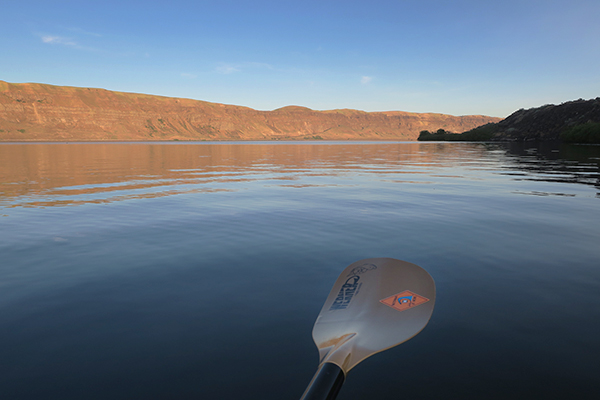 Sunrise over a calm Columbia River kayak fishing for smallmouth bass