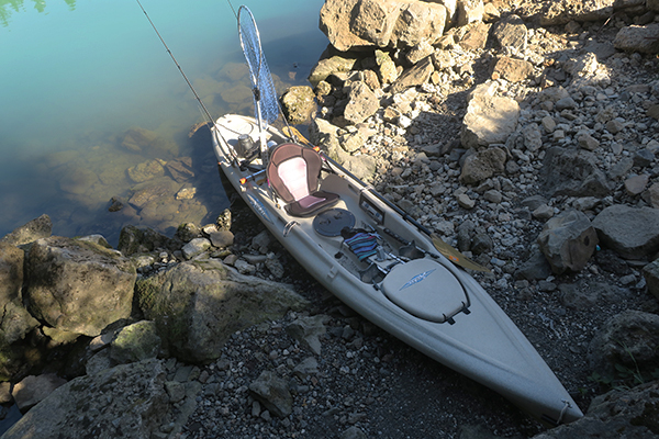 A rocky kayak launch at the base of a steep cliff