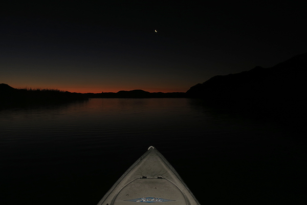 Crescent moon rises in the eastern desert sky over the Colorado River